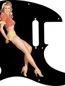 Blonde pinup girl wearing orange-red blouse with yellow panties and heals on a balck Telecaster pickguard