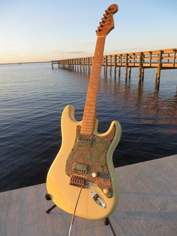 Fender Stratocaster with paisley pickguard displayed on the dock by the water